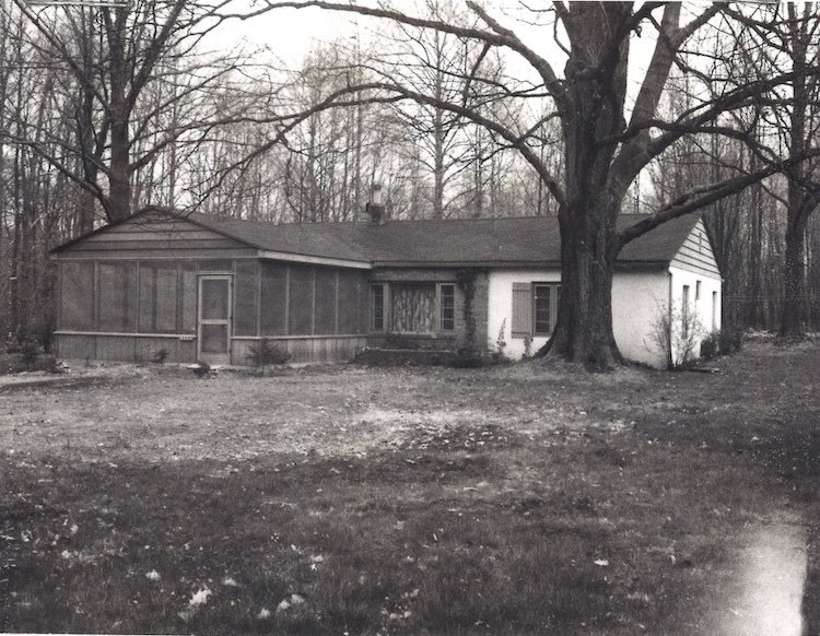 "Howe's client had a sentimental attachment to the old home, shown above in an old photo. It drew the architect's focus toward a minimal, open-plan renovation. ""It had the worst smell I had ever smelled in a house due to moisture,"" says Howe.  Photo 2 of 8 in Modern Cottage Renovation in Michigan"
