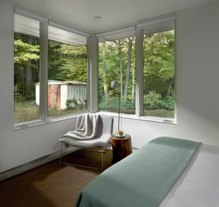 The modest bedroom looks towards the yard and part of the owner's garden. The table, by Jayson Home, holds a vintage lamp and is flanked by a Spring Lounge chair by Cappellini. Modern Cottage Renovation in Michigan - Photo 8 of 8