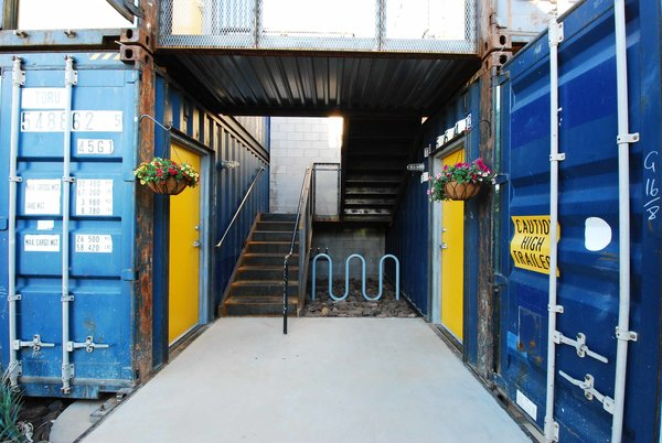 The containers are fused side-by-side, giving each apartment a 16-foot width. They are then stacked in four pairs with wrought, industrial-style exterior staircases in-between. To spare living space and installation headaches, a cinder block core houses utilities and a bathroom for each unit.