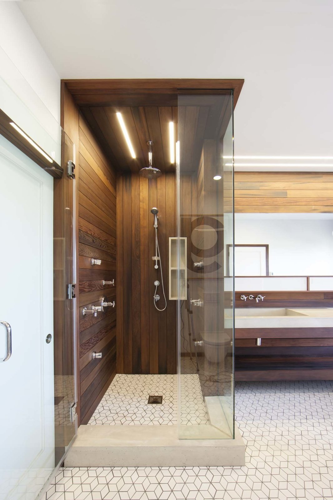 Lighting in the bathroom is provided by San Francisco-based Aion LED's modular fixture system. The linear lighting mimics the redwood siding. Tagged: Bath Room and Enclosed Shower.  Photo 10 of 10 in 10 Best Modern Showers to Inspire Your Bathroom Renovation from Warm Wood Modern Bathroom Renovation in San Francisco
