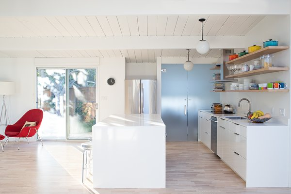 All the floors were redone in a light ash hardwood. The crisp interior paint is Benjamin Moore Super White. The kitchen cabinets are from Artistic Kitchens. A frosted glass door leads to the laundry room.