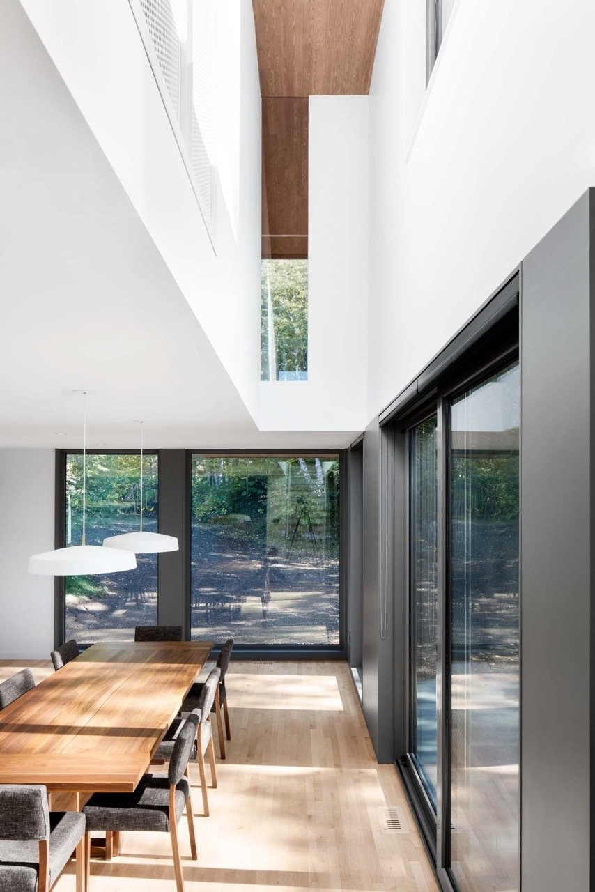 """""""Conceptually, all of the spaces in the house are connected to the kitchen and dining area by the stairwell, the second-floor catwalk, or through the glass in the living room,"""" said Rasselet. The dining room's walnut table and chairs are by Atelier LC2, and the Cliff light fixture is by Lambert & Fils.  Lounge by Jim Tattersall from House of the Week: Splash of Color in an Otherwise Minimalist Home"""