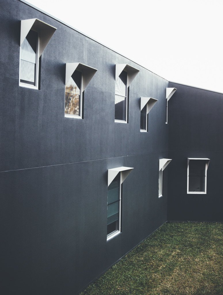 The cement exterior walls were painted in a dark color to blend in with the forest. Aluminum window frames add some texture to the facade.  Modern House Captures Panoramic Views in Australia by Allie Weiss
