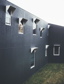 The cement exterior walls were painted in a dark color to blend in with the forest. Aluminum window frames add some texture to the facade.