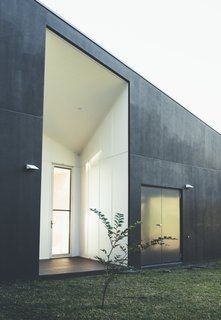 The house uses solar panels and water tanks to function off the grid. Its waste water is recycled and used for irrigation. This door is framed with a massive, geometric opening that's both dramatic and minimal at the same time.