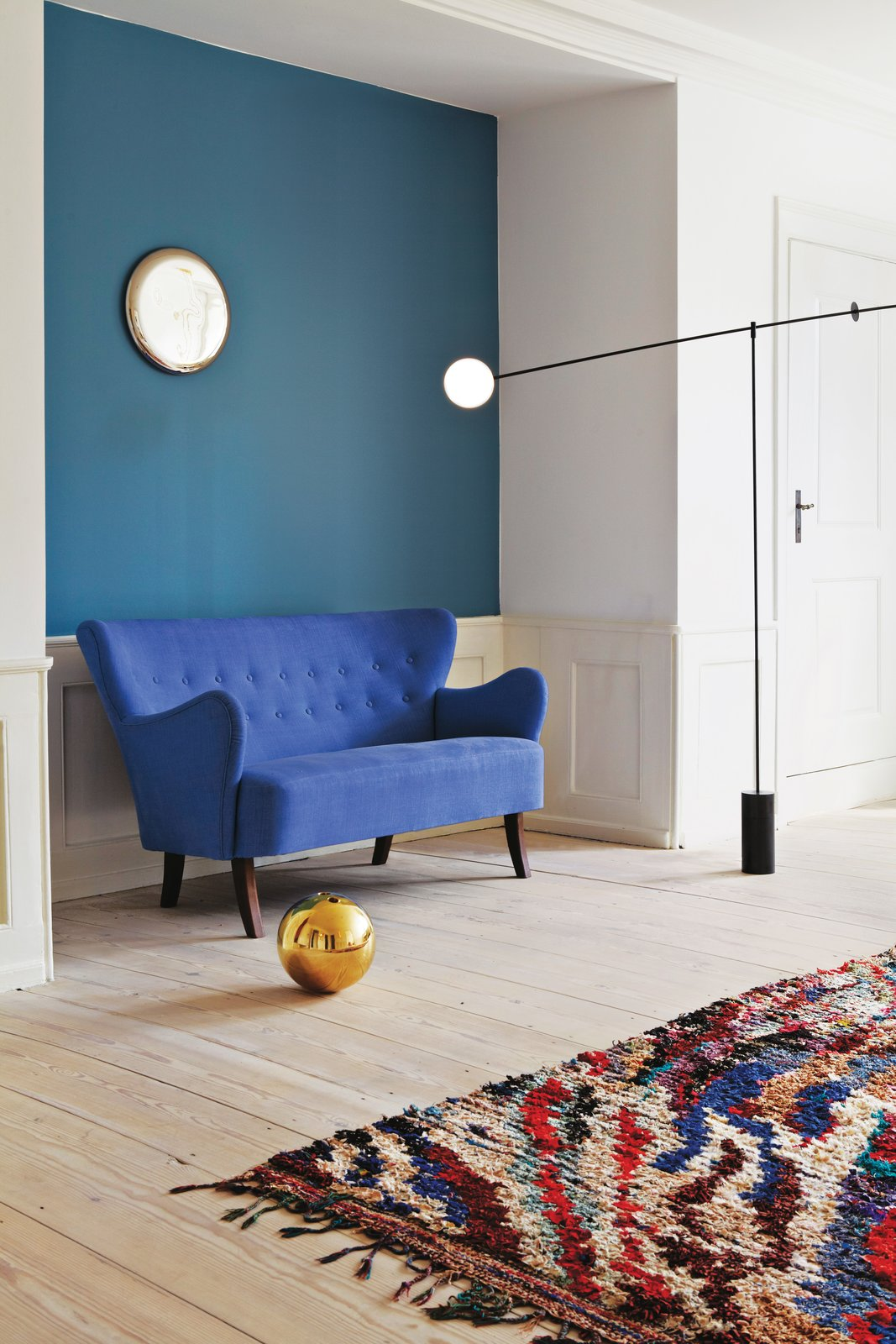 A Danish sofa, designer unknown, is set against an accent wall painted in Stone Blue by Farrow & Ball. As the local dealer for Anastassiades, the Apartment contains various pieces of his work, including the Mobile Chandelier 5 (2011), the Ball vase in cast brass (2006), and the wall-mounted Beauty Mirror (2010). The vintage Boucherouite rug is from Morocco. Photos courtesy the Apartment. 100+ Best Modern Seating Designs by Dwell