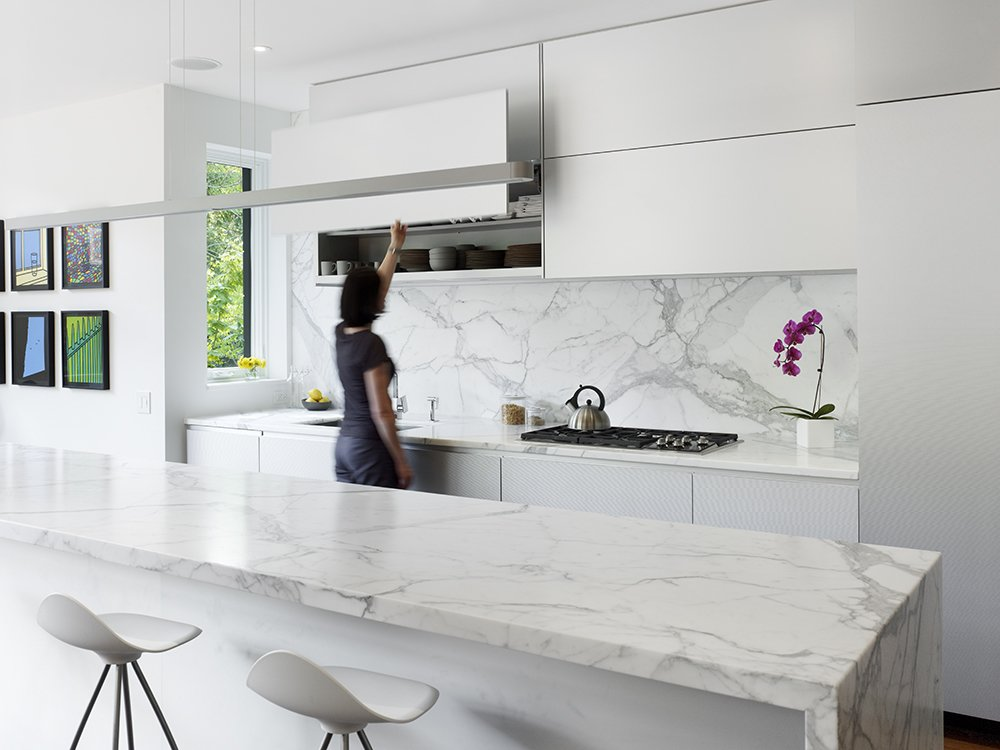 The kitchen contains Onda barstools by Stua from Design Within Reach that surround a 13-foot Calacatta marble island. Custom white aluminum cabinets float above the kitchen appliances by Miele with a stovetop from Wolf and a range hood by Airmec Bello. Tagged: Kitchen, Marble Counter, Cooktops, Stone Slab Backsplashe, and White Cabinet.  Photo 5 of 21 in Mad About Marble: 20 Kitchens and Bathrooms from A Cramped Boarding House Transformed Into an Open, Modern Home in Toronto