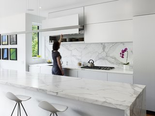 Mad About Marble: 20 Kitchens and Bathrooms - Photo 4 of 20 - The kitchen contains Onda barstools by Stua from Design Within Reach that surround a 13-foot Calacatta marble island. Custom white aluminum cabinets float above the kitchen appliances by Miele with a stovetop from Wolf and a range hood by Airmec Bello.