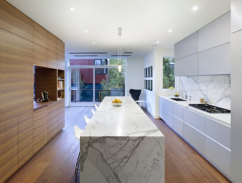 """The walnut unit between the kitchen and dining room ties into the fumed oak floor,"" Dubbeldam says. ""The rest of the materials in the house—glass, marble, stone—were selected to offset the wood."" Mad About Marble: 20 Kitchens and Bathrooms - Photo 3 of 21"