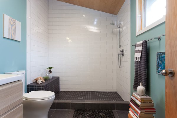 The bathroom features white and black tile and a small rock bed.