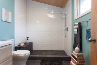 Renovation: A Sunny Berkeley Bungalow Invites the Outdoors In - Photo 4 of 5 - The bathroom features white and black tile and a small rock bed.