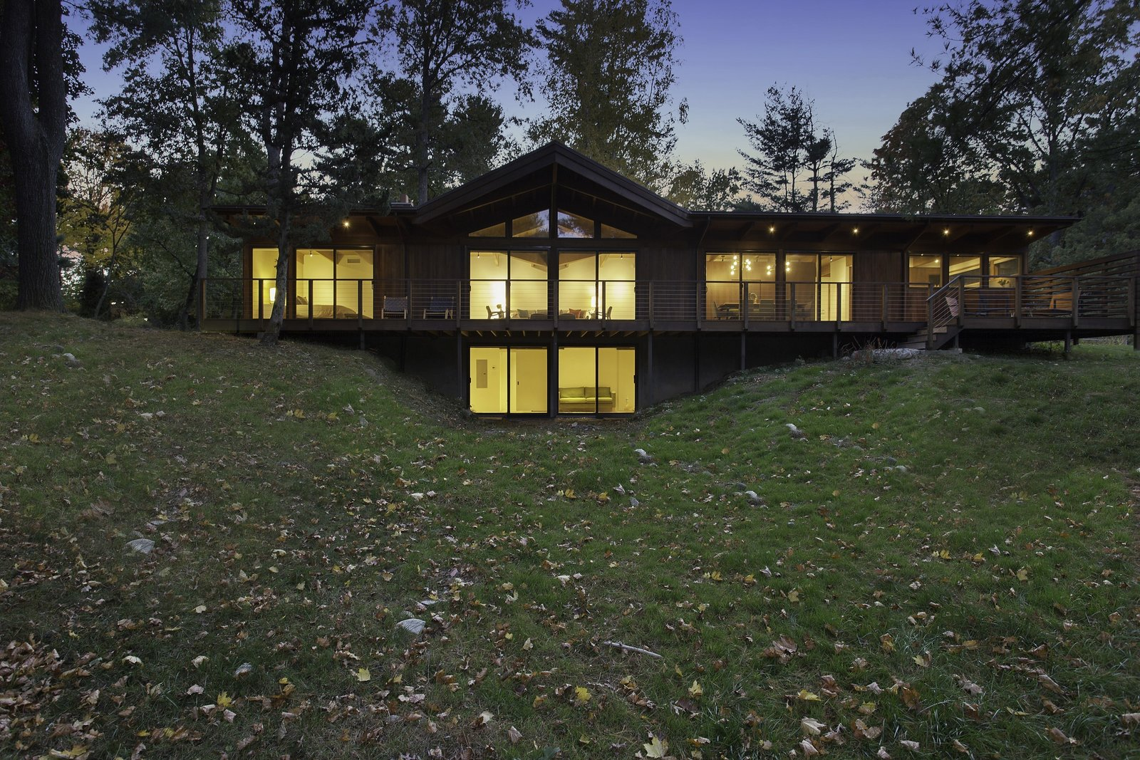 """""""The use of the structural insulated panels for the roof allowed us to keep the exposed post-and-beam look, which is a midcentury trademark, while making the house energy-efficient,"""" Schultz said. Douglas firm beams and soffits support a SIPS roof, which shades Andersen Windows & Doors. The deck, made of red meranti, overlooks a nearby pond."""
