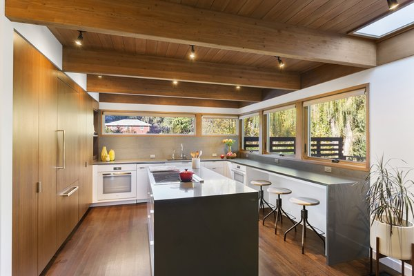 Custom cabinetry with a walnut veneer is across from Caesarstone countertops and a Basaltina tile backsplash by Stone Source. Photo 5 of City Skyline modern home