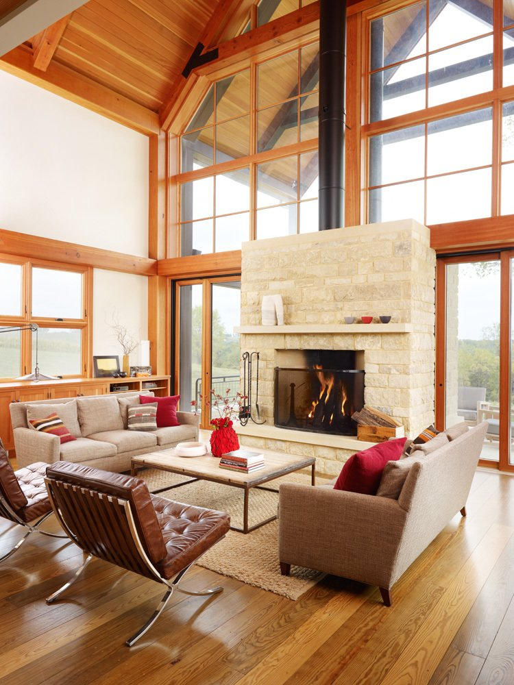 The design pairs durable steel construction on the outside with warmer timber frames on the interior. At the center of the expansive glass wall stands a two-sided fireplace that can heat the deck outside and living room within. Seen here are a Restoration Hardware Brickmaker's coffee table and sofas from Lee Industries.