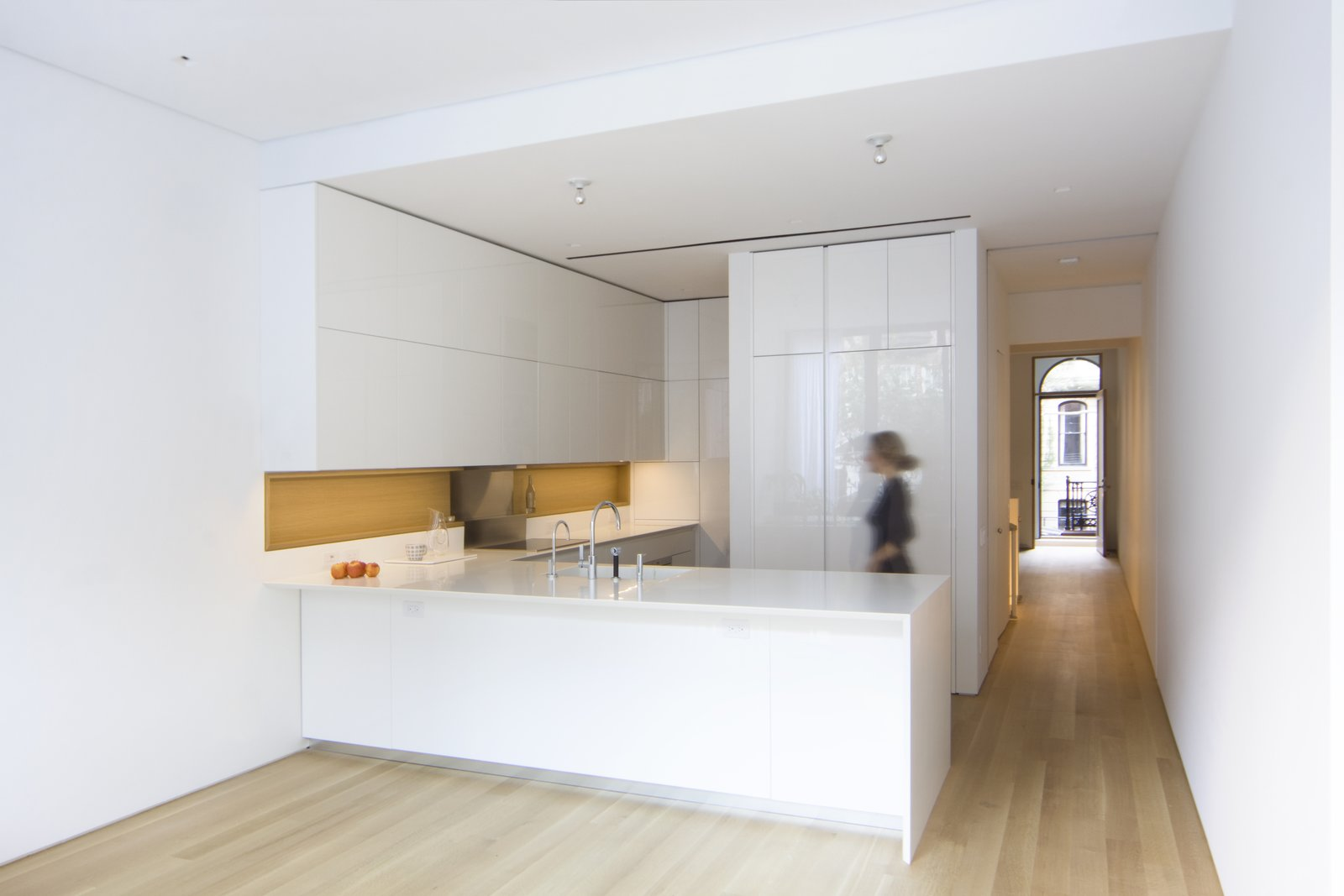 The kitchen has views to the historic main entrance and features lacquered cabinets and an integrated wooden niche custom-designed by the architects with GD Cucine. Matching Corian countertops and an integrated sink maintain a minimal aesthetic alongside appliances by Gaggenau and Miele. Tagged: Kitchen, Engineered Quartz Counter, White Cabinet, Light Hardwood Floor, Ceiling Lighting, and Undermount Sink. White Oak by Maura Lucking