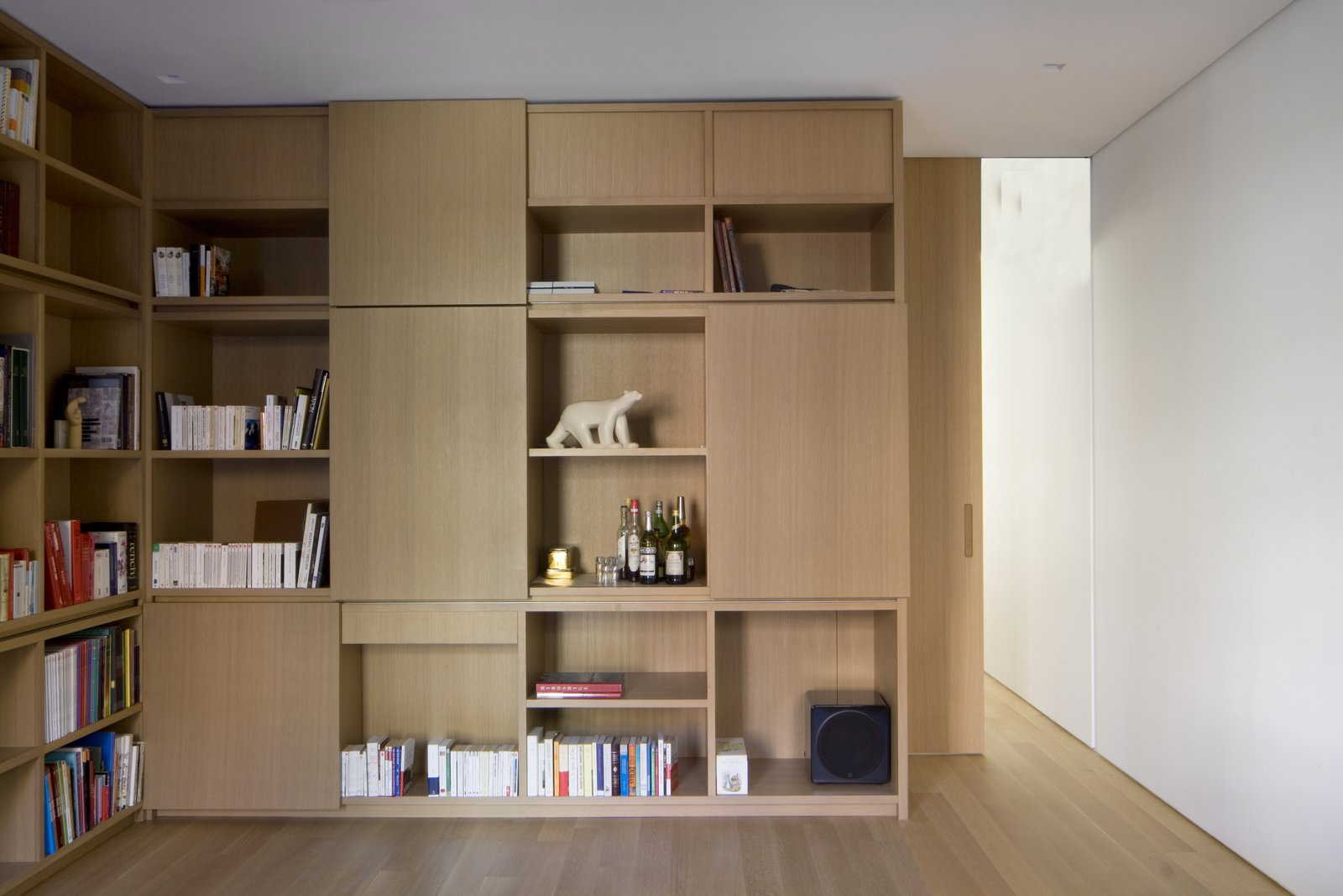 More custom millwork features asymmetrical shelving and closed storage spaces with sliding panels on HAFELE sliding tracks. A 10-inch matching pocket door provides privacy when desired without interrupting the space.
