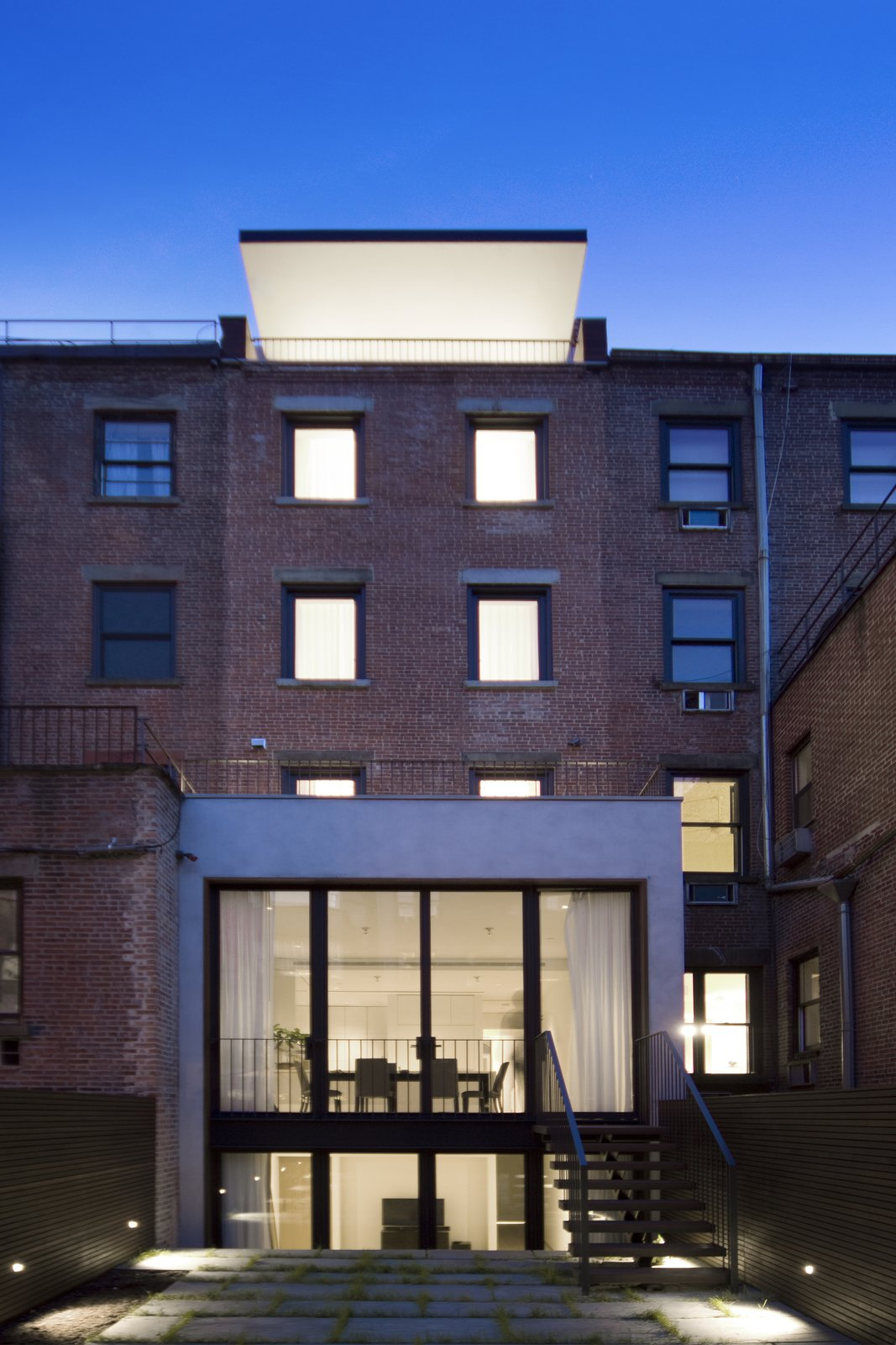The restored brick rear facade contrasts with the extended footprint of the first two floors and a dramatic cantilevered penthouse roof. Blue stone pavers, infilled with grass, finish the patio while a black steel stair leads to the kitchen.