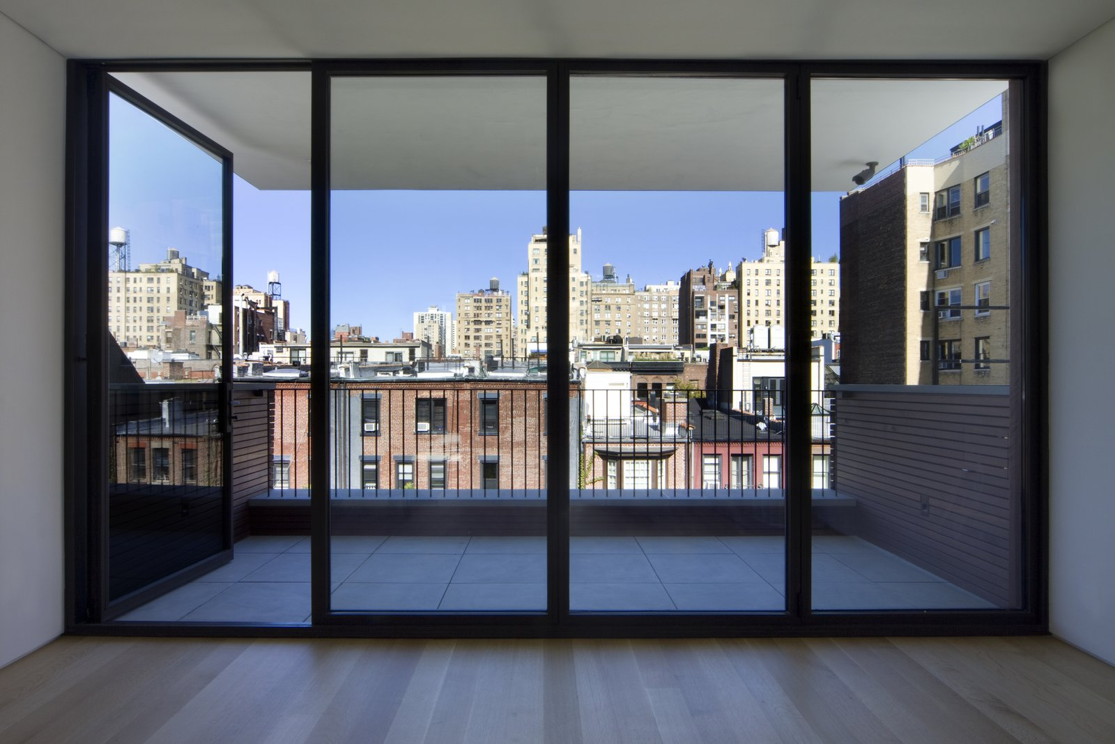 "The fifth story was added late in the design process because ""our clients wanted to have their own private space,"" Ruggieri says. The stunning north view across Manhattan from the penthouse is one of the home's best features, outlined in black steel windows by Optimum.  White Oak by Maura Lucking"