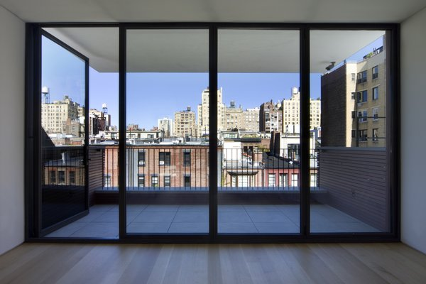 "The fifth story was added late in the design process because ""our clients wanted to have their own private space,"" Ruggieri says. The stunning north view across Manhattan from the penthouse is one of the home's best features, outlined in black steel windows by Optimum. Photo 10 of White Oak modern home"