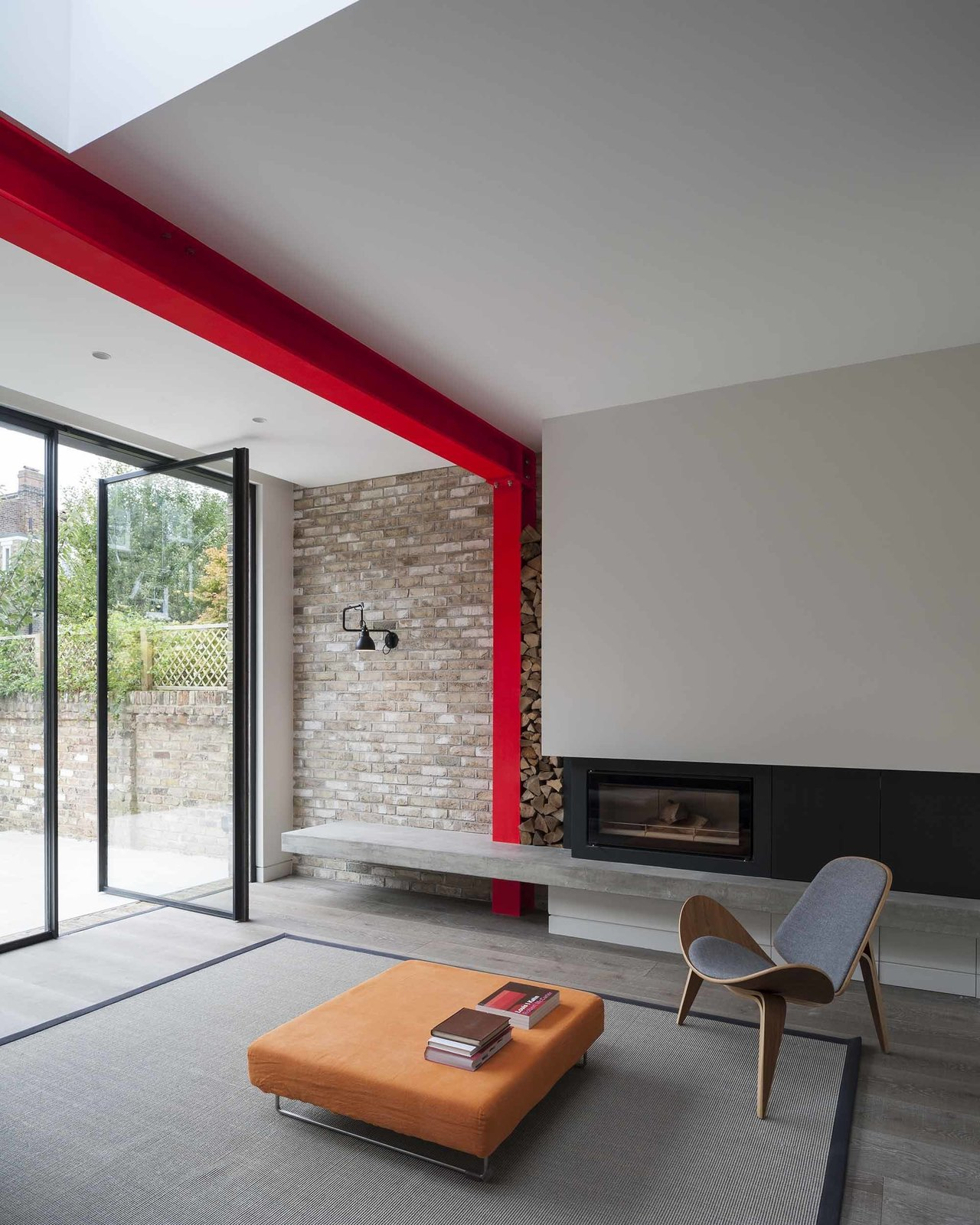 A Hans Wegner Shell chair by Carl Hansen & Søn outfits the living room, which is defined by a steel beam painted sharp red.  97+ Modern Fireplace Ideas by Dwell from A London Town House Renovation Beaming with Personality
