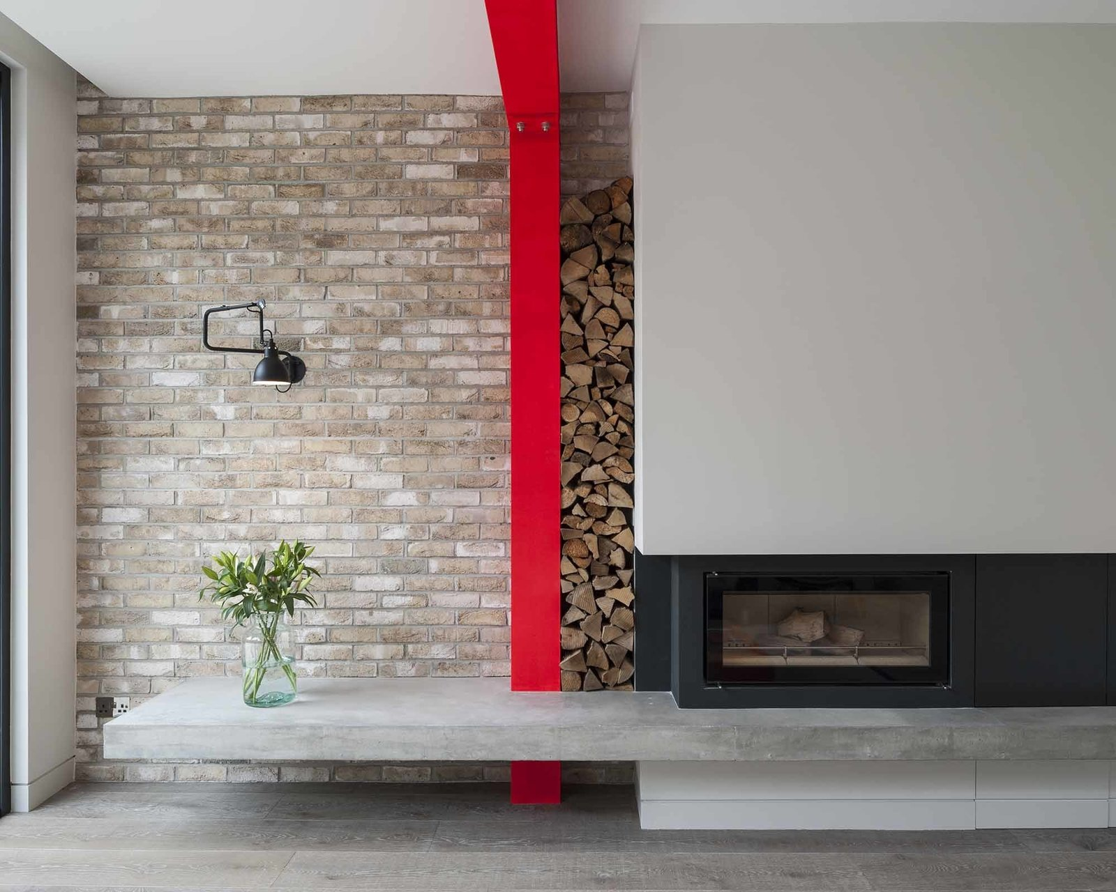 The overhanging concrete plinth acts as a hearth or, as Tigg imagines it, a sort of contemporary inglenook. Wood piles neatly between the beam and wall. The fireplace, a Stovax Riva 2, is flanked by a Lampe Gras wall lamp.  97+ Modern Fireplace Ideas by Dwell from A London Town House Renovation Beaming with Personality