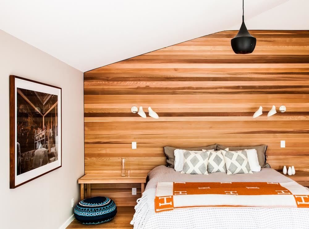 """""""We brought the cedar siding of the exterior inside strategically, both to blur inside and out and to give texture,"""" Young says. """"Simple forms and clean lines, if done right, have a calming effect and nicely contrast the furnishings."""" The master bedroom features the same western red cedar as the exterior, and lighting by David Weeks Studio."""