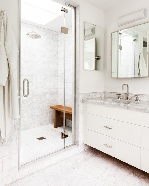The master bathroom's countertops are detailed with the same Carrara marble seen in the kitchen. The faucet and shower trims are by Kallista.