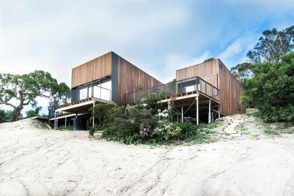 "The home, clad in natural Australian timber, enjoys a sense of lightness thanks to slender columns that let it float over the dunes. The driveway and entry, at the rear of the building, have an understated design to build to the interior's magnificent ocean views. Firm director Phil Snowdon explains, ""By creating an architectural form that draws your eye and leads you up the steep driveway, we could engage new visitors in a welcoming process that first reveals the object and then slowly reveals the main event, being the view."" Photo  of Martha modern home"