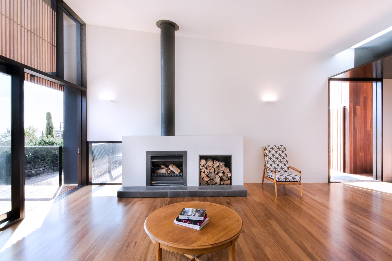 Immediately to the right of the entry is the main living space, which features a Jetmaster 700D wood-burning fireplace. Tagged: Living Room, Wood Burning Fireplace, Standard Layout Fireplace, Medium Hardwood Floor, Chair, Coffee Tables, and Wall Lighting.  Lounge by Jim Tattersall from Martha