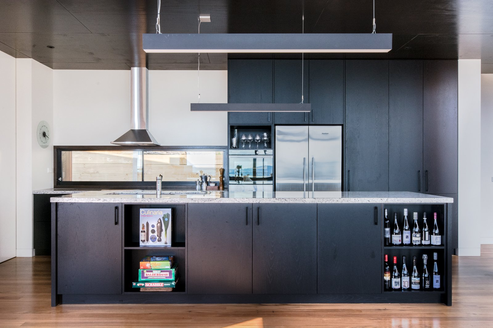 A granite island countertop and black American oak cabinetry are a winning combination for the utilitarian kitchen. The sleek kitchen pendant lights are Matric-P4's from Lightnet.  Photo 5 of 8 in An Australian Beach Home with Stunning Ocean Views from Martha