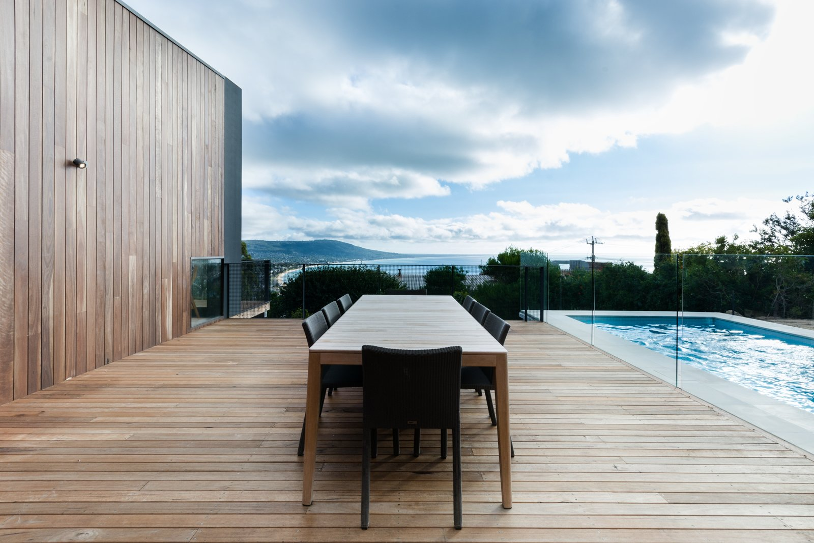 A Mood Outdoor Table by Studio Segers for Tribù is surrounded by Terra Outdoor Chairs by Bram Bollen, also for Tribù. They rest atop silvertop ash hardwood decking. Tagged: Outdoor, Large Pools, Tubs, Shower, Swimming Pools, Tubs, Shower, Large Patio, Porch, Deck, Wood Patio, Porch, Deck, Trees, Back Yard, and Metal Fences, Wall.  Photo 3 of 8 in An Australian Beach Home with Stunning Ocean Views from Martha