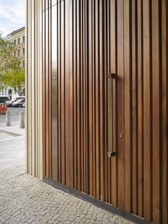 The wooden door mimics the structure's textured exterior.