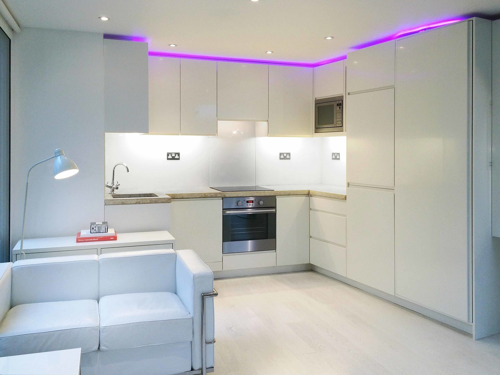 The kitchen cupboards have the same high-gloss cladding as the collapsible workstation. The countertop is polished concrete from Shaw Interiors, and the lighting is inset LED's. The space also features recessed ceiling speakers from B&W.  Photo 7 of 7 in A Tiny Live/Work Addition Crowns a Historic London House