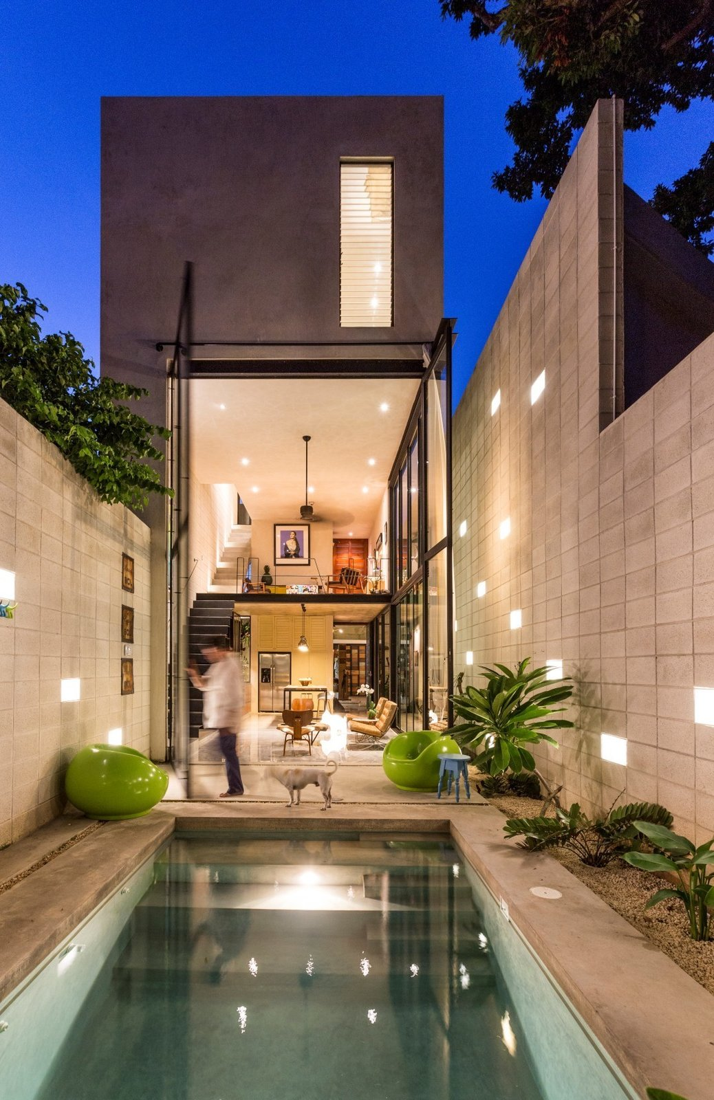 """The back of the home glows at night as the giant, two-story glass doors swing open to remove the barrier between inside and out. A polished concrete patio deck and pool, along with a simple block perimeter wall, make smart use of available materials. The pool acts as a passive conditioning tool, cooling air before it enters the house. The block wall is positioned 31 inches from the house, creating a gap or """"air chimney"""" that allows air to circulate up and away from the home, while simultaneously letting light filter down."""