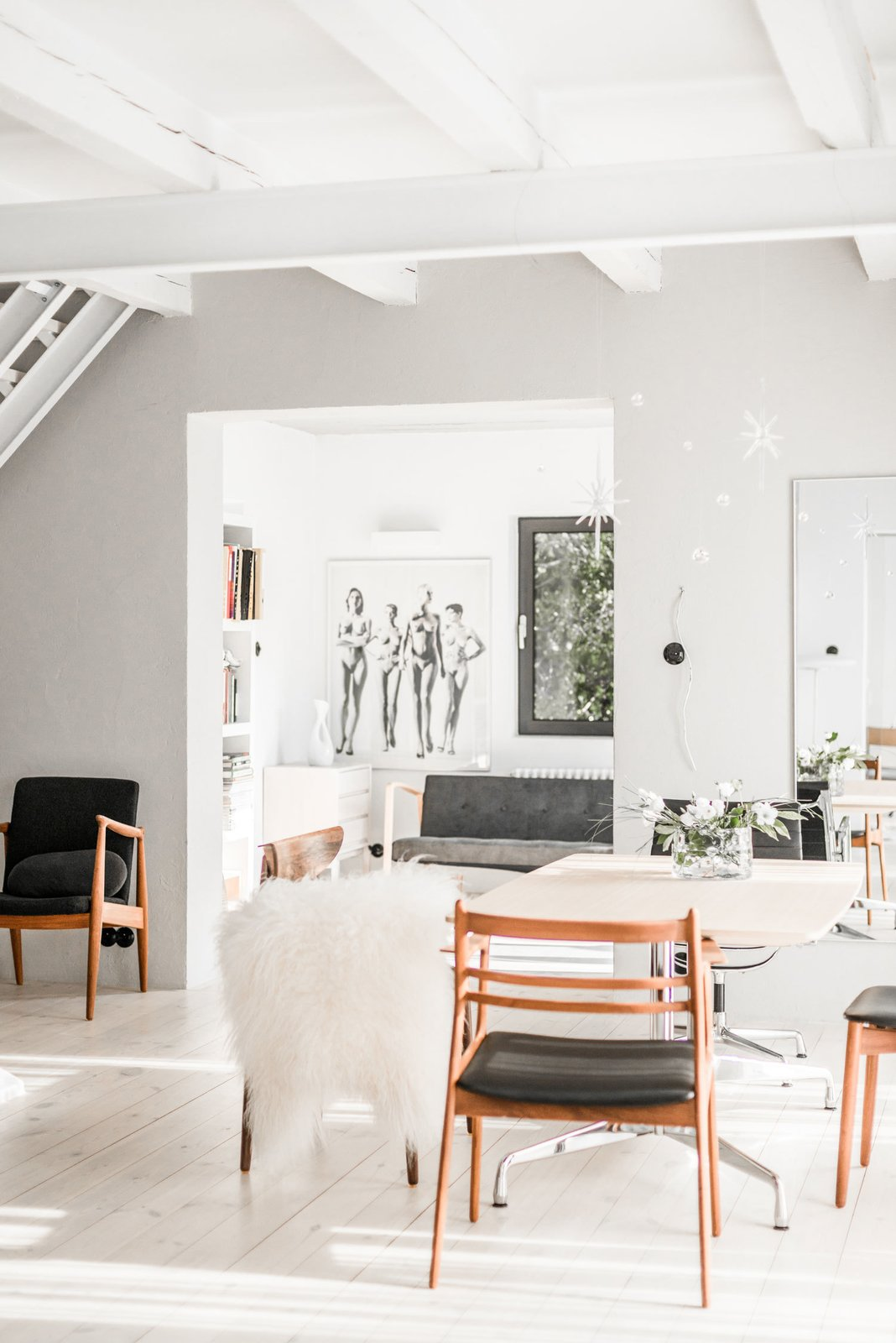 The dwelling showcases the designer's collection of Danish chairs and loungers from the 1940s, 50s, and 60s — including pieces designed by Kofod Larsen, J.L Moller, Harry Ostergaard, Bruno Mathsson, and Hans J. Wegner. Tagged: Dining Room, Table, Chair, and Light Hardwood Floor.  Photo 6 of 10 in A Run-Down Farmhouse Becomes a Sleek Modern Retreat