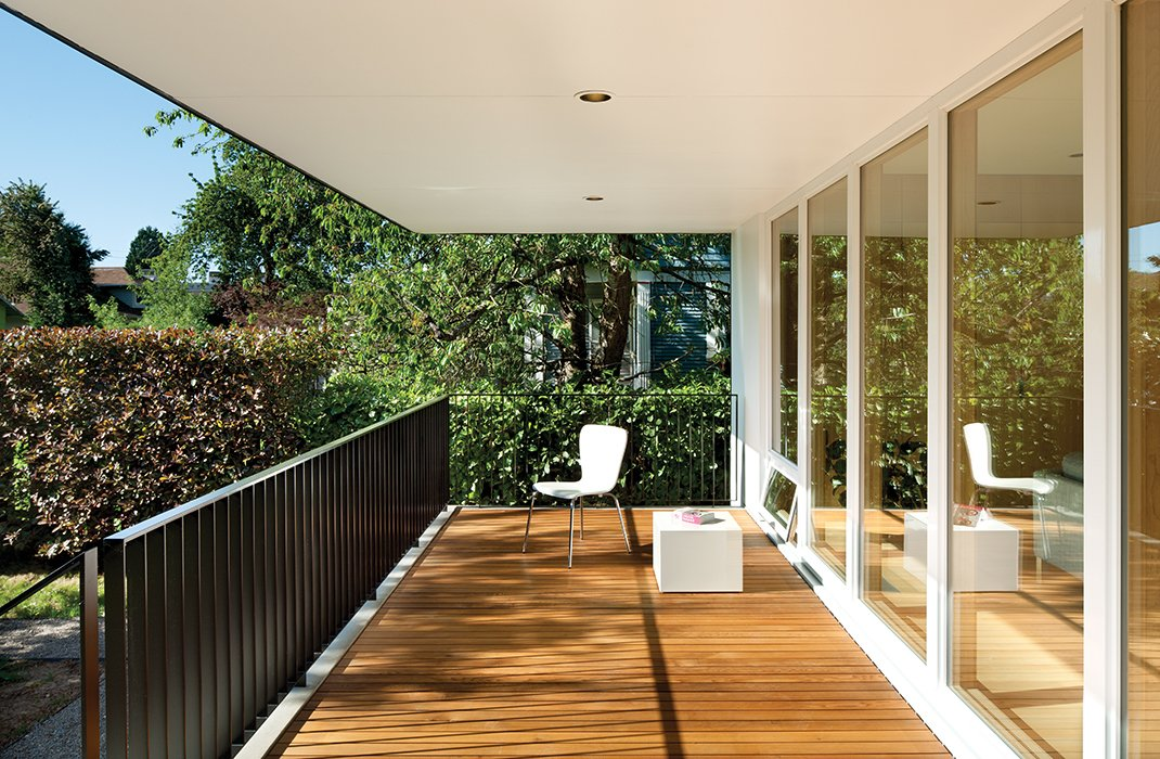 "Floor-to-ceiling windows from Sierra Pacific offer views across a cedar deck to the backyard. Oakley says he and Waechter asked themselves, ""How would we build something that's functional and warm and utilitarian, and have some vestige of familiar architectural reference?"" Tagged: Outdoor and Wood Patio, Porch, Deck.  Photo 6 of 9 in An Industrial Designer's House Blends Economy and Simplicity"