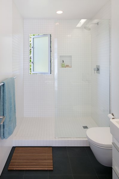 The master bathroom is clad in inexpensive tile from Daltile. The wall-hung toilet is by Duravit.