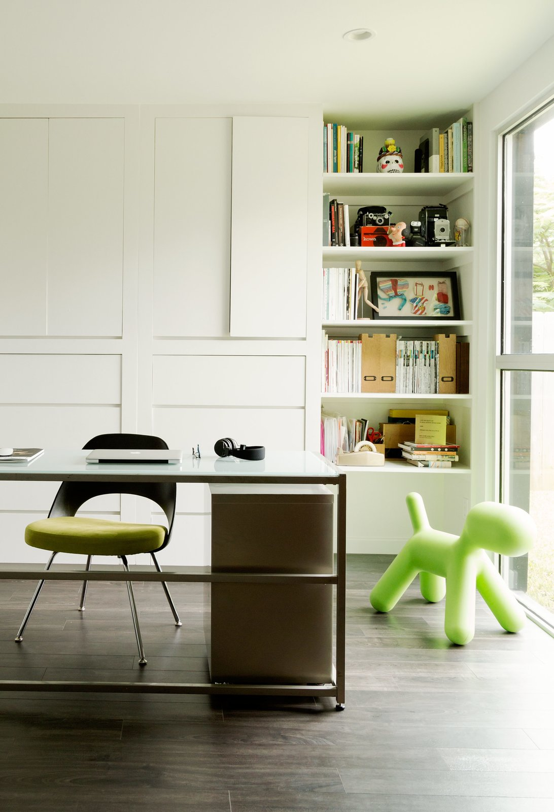 The office space doubles as a play area, so the parents can keep an eye on the kids while they work. The Saarinen Plastic Back side chair from Knoll was a gift from a friend. Tagged: Office, Chair, Desk, Storage, Bookcase, Shelves, Dark Hardwood Floor, and Study.  Midcentury Homes by Dwell from A Modern Renovation Connects to a Traditional Texas Town Through a Glass Wall