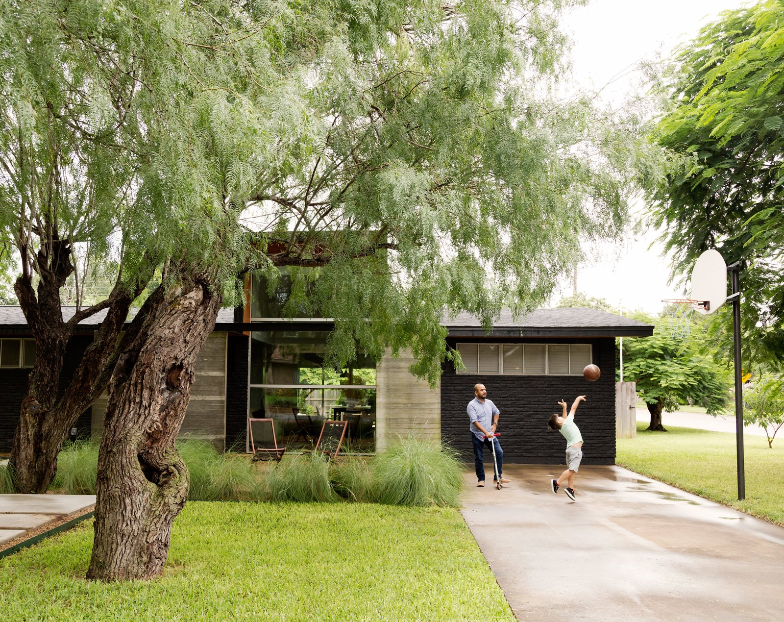 López insisted on a concrete pathway that winds through the trees, so visitors don't have to enter through the driveway. Tagged: Exterior, Concrete Siding Material, and Brick Siding Material.  Photo 2 of 10 in A Modern Renovation Connects to a Traditional Texas Town Through a Glass Wall