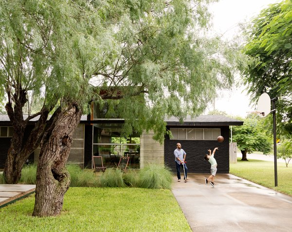 A Modern Renovation Connects to a Traditional Texas Town Through a Glass Wall - Photo 2 of 10 - López insisted on a concrete pathway that winds through the trees, so visitors don't have to enter through the driveway.