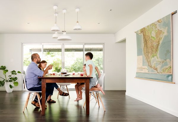 In the dining room, the family gathers beneath a cluster of IKEA Ranarp pendants.