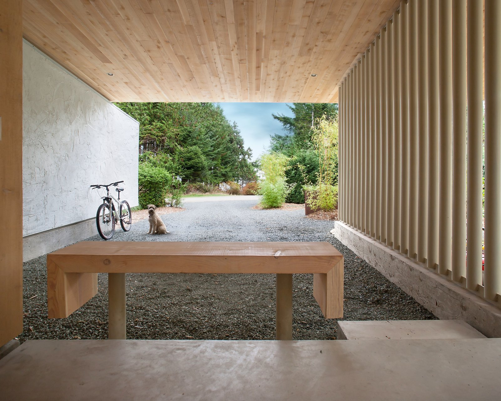 """""""The goal I had was for a new building to be sympathetic to a quirky, soulful little cabin that was not modern in many ways,"""" Jones says. He mirrored the original home by incorporating the same cement stucco, painted pure white, with Douglas fir soffits. Two Douglas fir trees had to be cut down during construction, and they were repurposed throughout the home—including for this bench."""