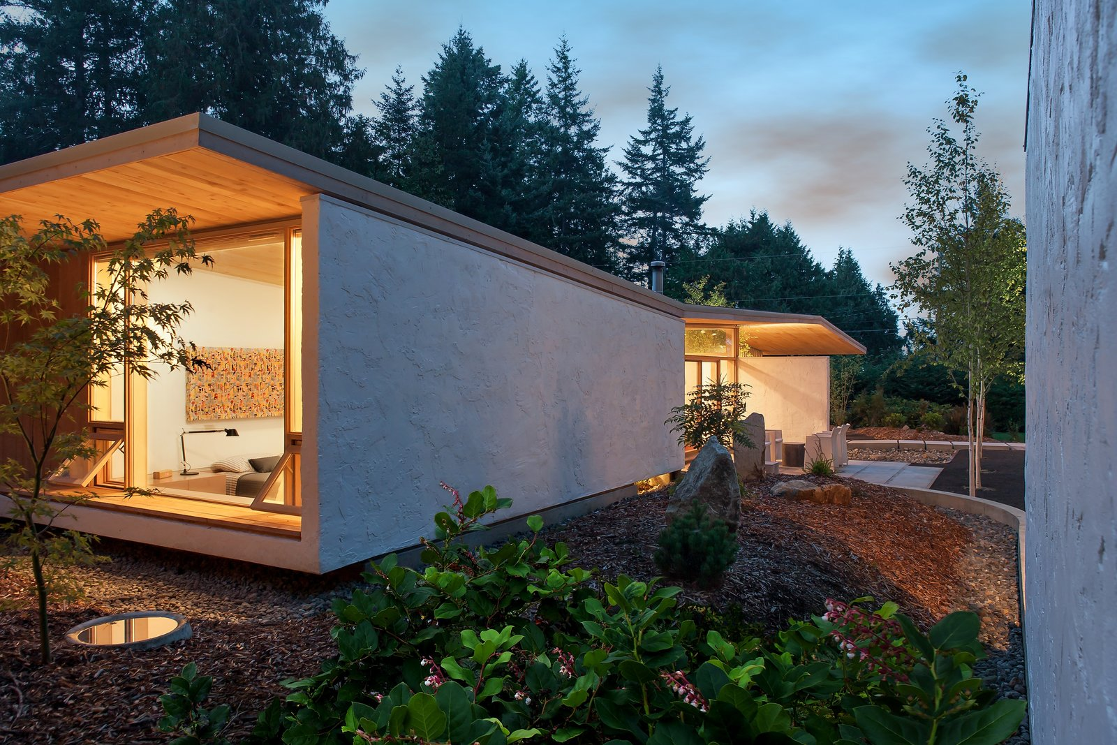 """""""[The house] avoids the mass or heaviness of too much timber construction, so with a few hidden steel beams, it seems to float and hover over the site in a delicate way,"""" Jones says. Salal, a native plant to the Pacific Northwest, and fern act as the site's groundcover."""