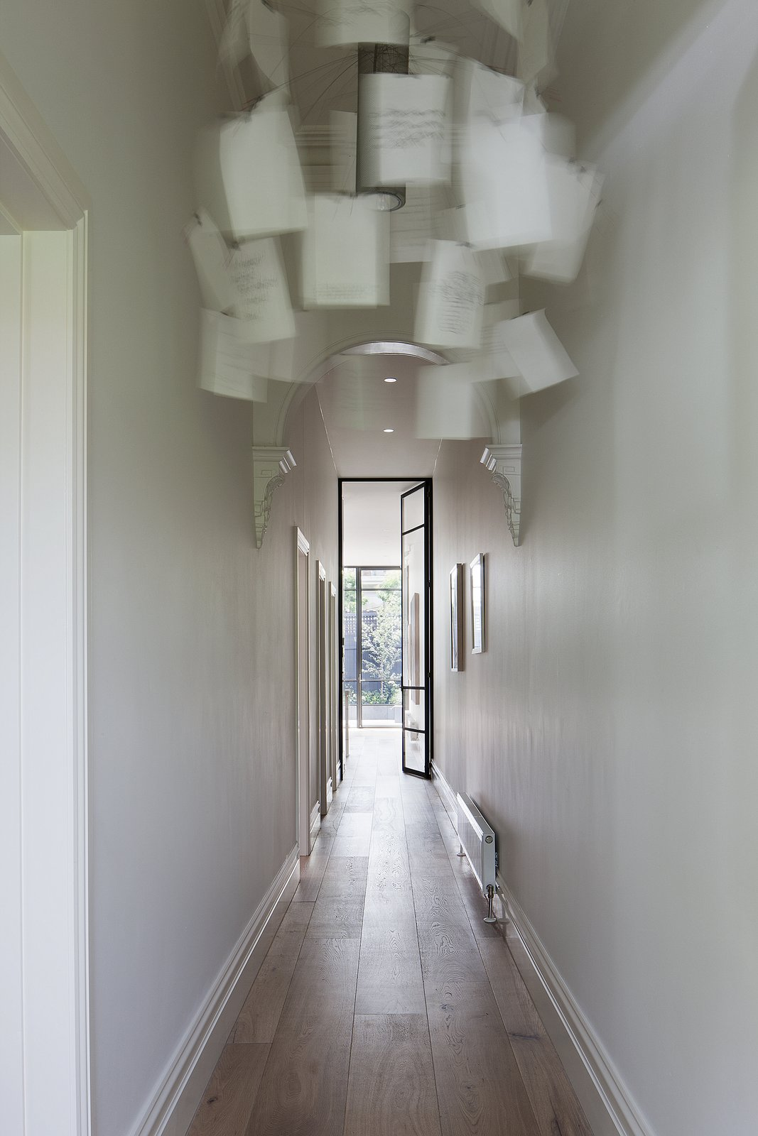 An Ingo Maurer Zettel'z 5 chandelier hangs in the entry hallway; sunlight from the home's expansive backyard is already visible on the white smoked oak floors. Tagged: Hallway and Medium Hardwood Floor.  Seclusion by Caroline Wallis