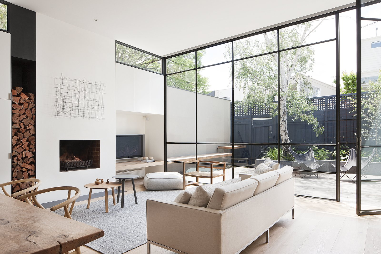 "The designers explain, ""These steel windows played an integral part in making the interior feel larger and more open by blurring the boundaries between the interior and exterior."" A grey Halcyon Lake area rug, an oak chair from MAP, and Hans Wenger Wishbone chairs make for a simple, neutral palette. The painting over the fireplace is by Kate Hendry. Tagged: Living Room, Chair, Sofa, Coffee Tables, Light Hardwood Floor, and Wood Burning Fireplace.  Living Rooms by Lara Deam from Seclusion"