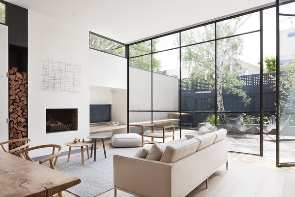 """The designers explain, """"These steel windows played an integral part in making the interior feel larger and more open by blurring the boundaries between the interior and exterior."""" A grey Halcyon Lake area rug, an oak chair from MAP, and Hans Wenger Wishbone chairs make for a simple, neutral palette. The painting over the fireplace is by Kate Hendry."""