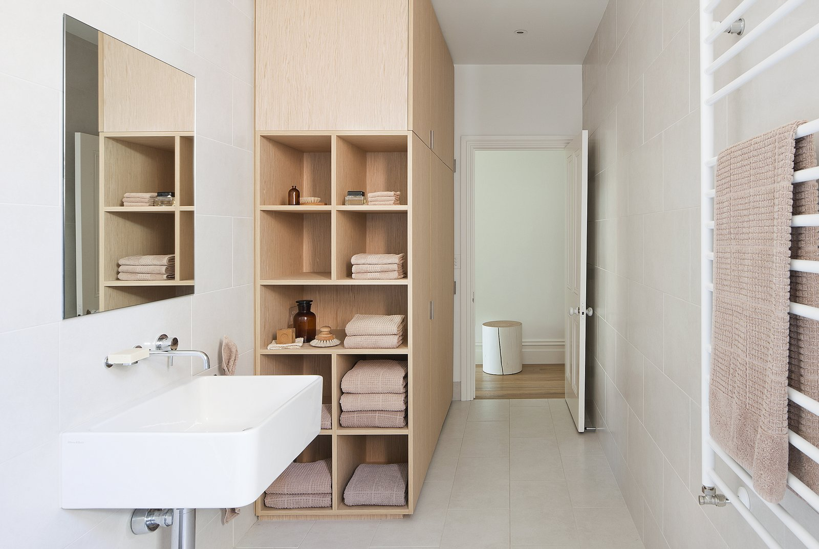 To stay within the budget, the designers decided to forgo natural stone in the bathrooms in lieu of simple vitrified tile. The bathroom isn't without its luxuries, however, as evidenced by the heated towel rail from Hydrotherm. Tagged: Storage Room, Wall Mount Sink, Ceramic Tile Wall, Ceramic Tile Floor, and Shelves Storage Type.  Seclusion by Caroline Wallis