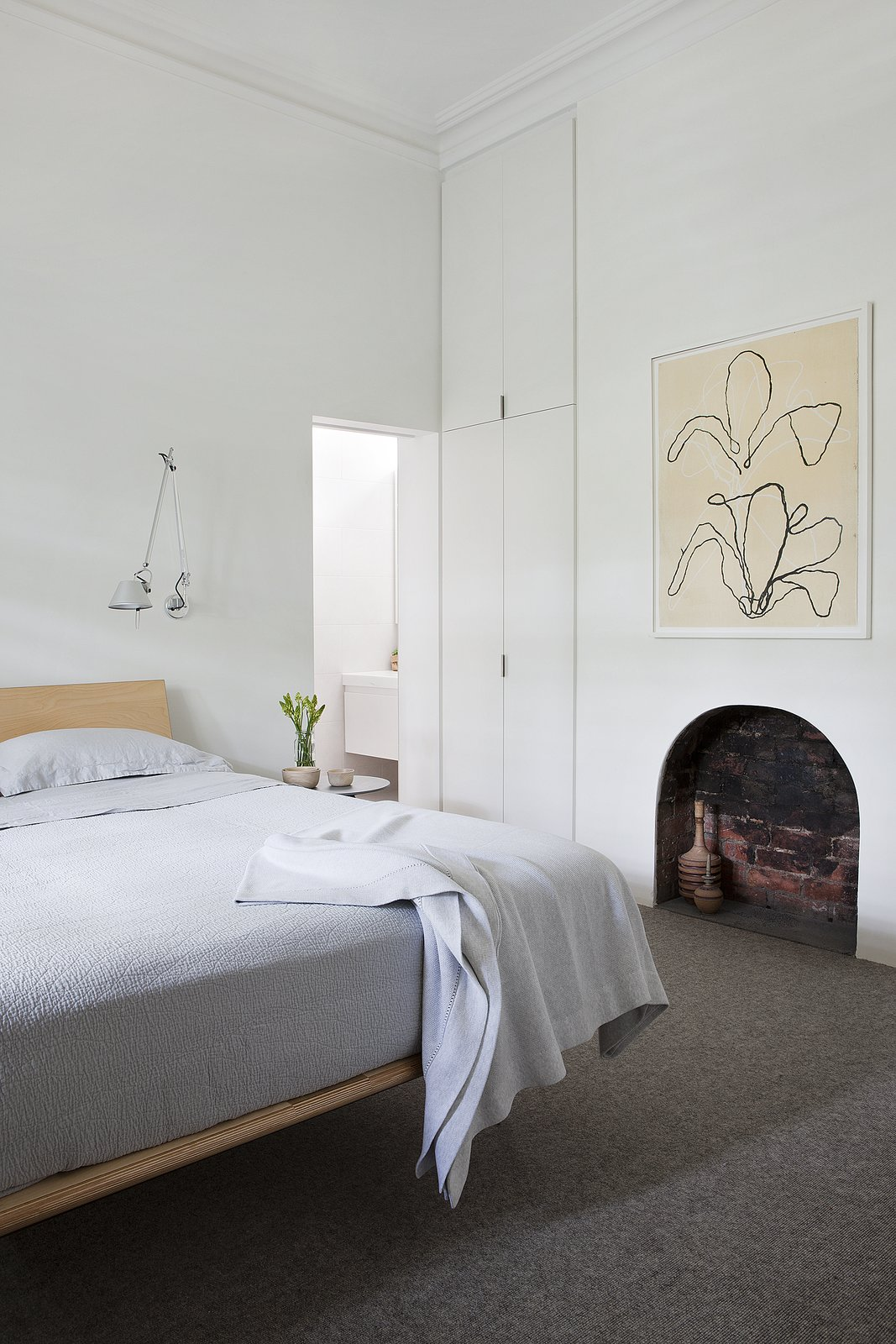 """[W]e didn't need a huge space for our clients to live in harmony, it just needed to be a well thought out space,"" says the architects. A V Leg Bed by George Nelson is a classic addition to the bedroom, along with Tolomeo wall mounted luminaires from Artermide. The artwork is from David Band. Tagged: Bedroom, Bed, Wall Lighting, and Carpet Floor.  Seclusion by Caroline Wallis"