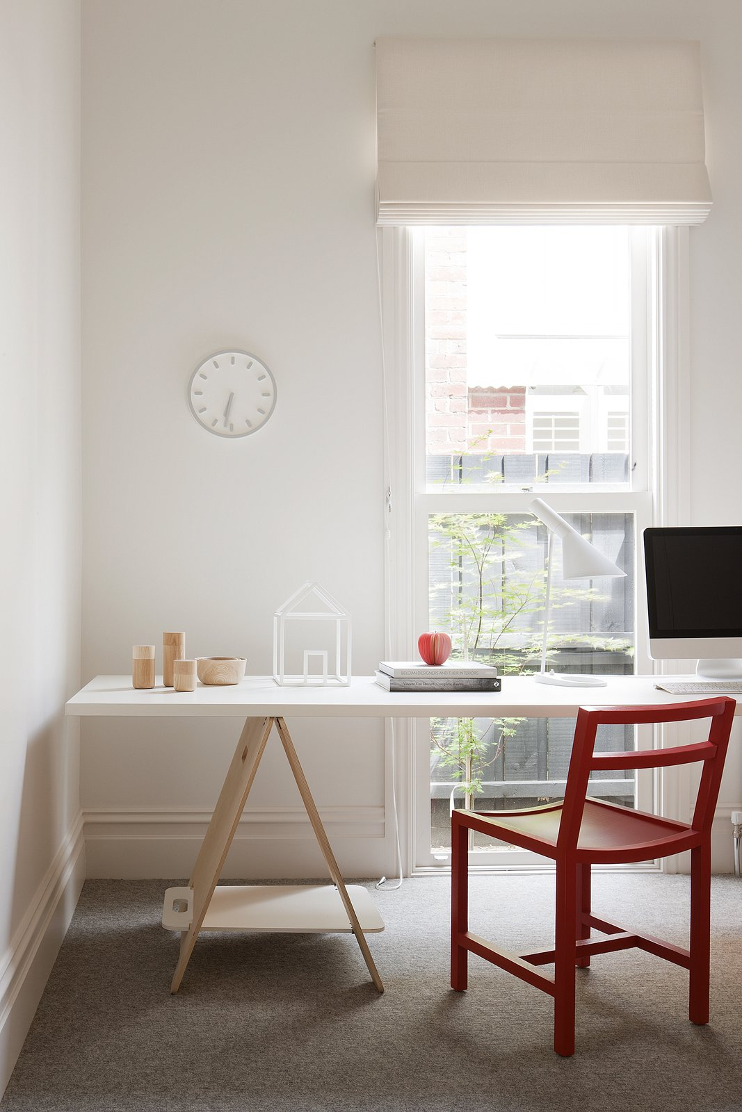 The study has a fun, playful atmosphere thanks to a red Square Dining Chair from MAP, a Tempo wall clock by Naoto Fukasawa for Magis, and house sculpture also from David Band.