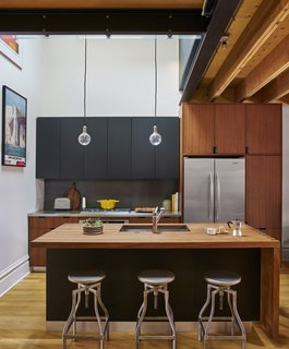 A Chicago Renovation Taps Into its Attic to Almost Double its Square Footage - Photo 3 of 8 - The kitchen features Schoolhouse Electric & Supply Co. pendant lights and Crate and Barrel stools. The woodblock island's leaf, at the far right, can lift upwards to expand the table when work or hosting demands it. The faucet is from KWC.